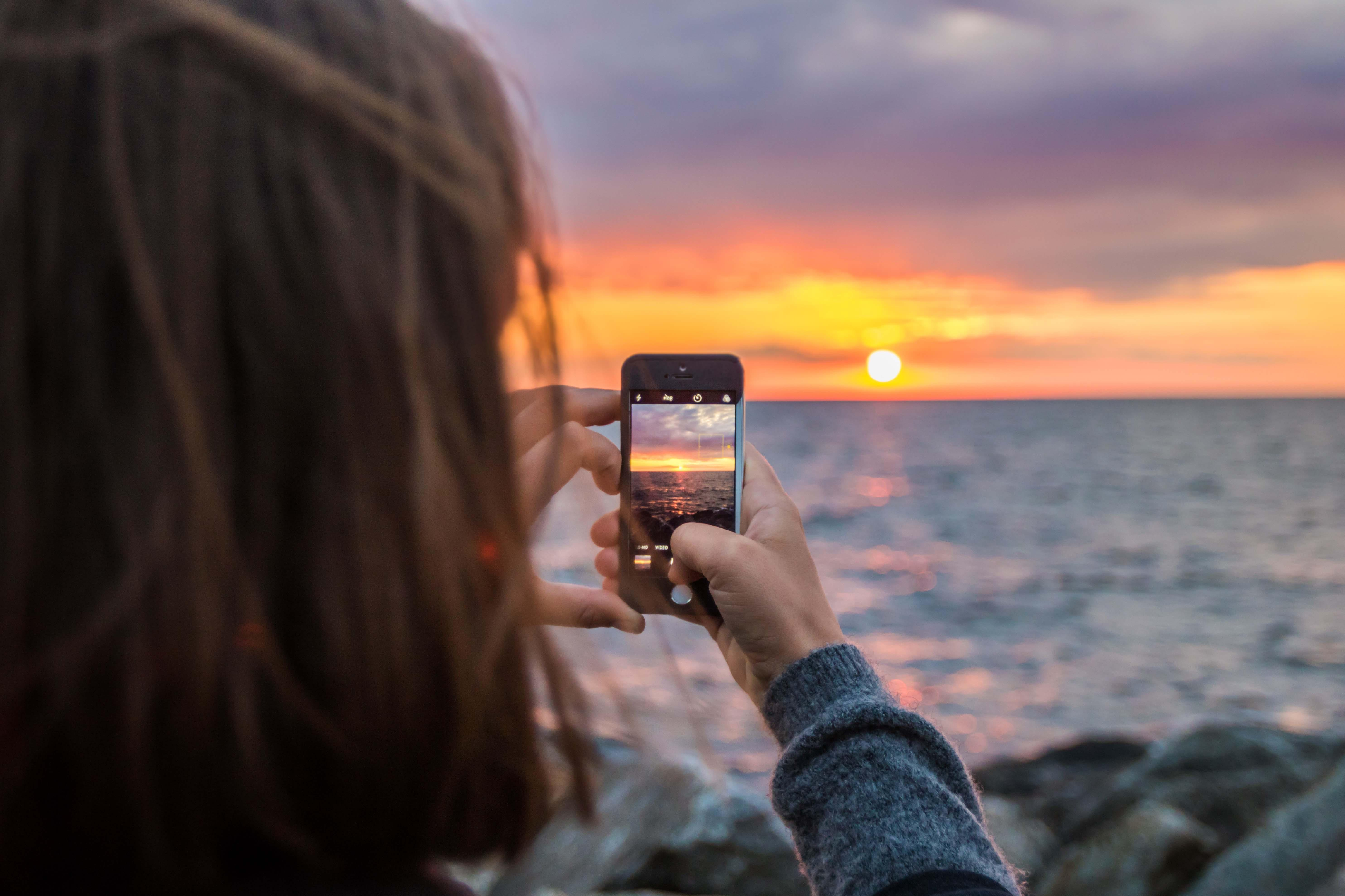 Woman using camera phone to take picture of sunset